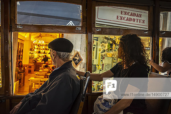 Passengers inside a tram on a street passing storefronts; Lisbon  Portugal