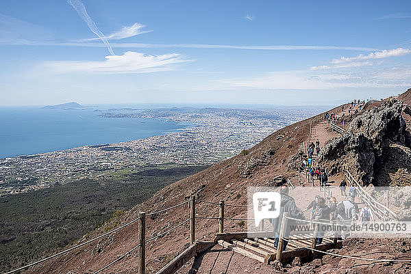 Tourists hiking on a trail with a view of Naples from Mount Vesuvius; Naples  Italy