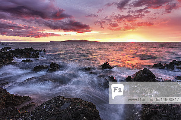 Soft water over lava rocks with a red sunset; Makena,  Maui,  Hawaii,  United States of America