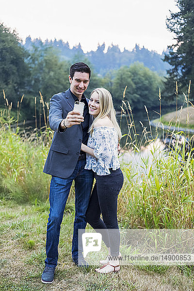 A young couple taking a self-portrait with a smart phone; Bothell  Washington  United States of America