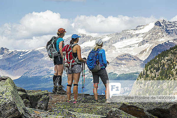 Three female hikers on a mountain rock overlooking mountain vista in the background; British Columbia  Canada