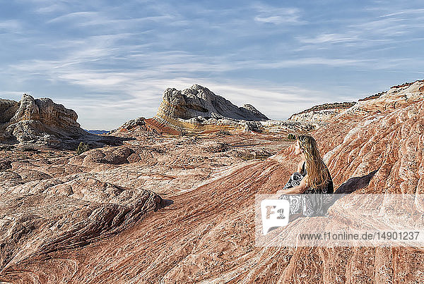 A woman sits on a rock formation enjoying the view at White Pocket  Vermilion Cliffs National Monument; Kanab  Arizona  United States of America