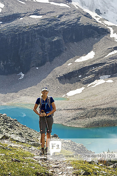 Female hiker on mountain pathway with a colourful alpine lake and mountain cliffs with snow in the background; British Columbia  Canada