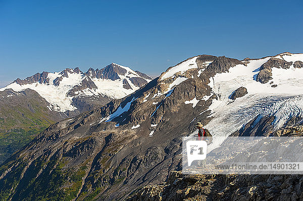 A man hiking near the Harding Icefield Trail with the Kenai Mountains and an unnamed hanging glacier in the background  Kenai Fjords National Park  Kenai Peninsula  South-central Alaska; Alaska  United States of America