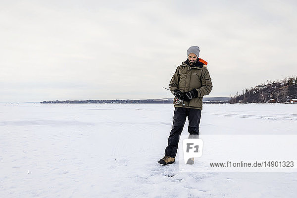 Man patiently waiting for a bite while ice fishing at Wabamun Lake; Wabamun  Alberta  Canada