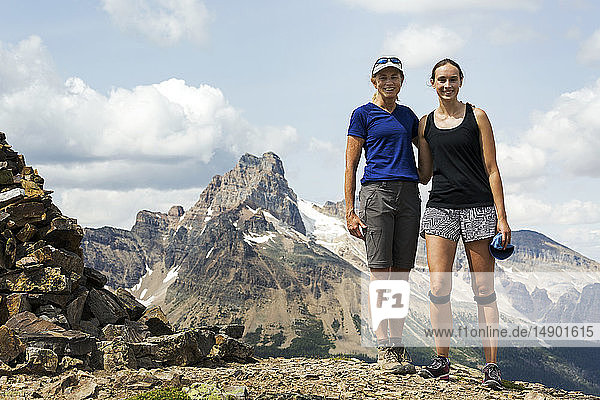 Two female hikers standing on rocky mountain top with mountain  blue sky and clouds in the background; British Columbia  Canada