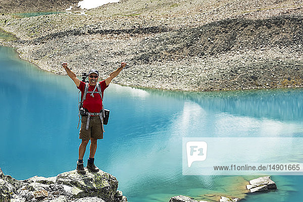 Male hiker standing on a large rocky area with a colourful alpine lake and rocky shoreline in the background with arms up in the air; British Columbia  Canada