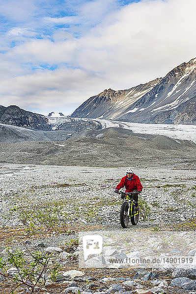 A man riding his fatbike in Gulkana Glacier Valley; Alaska  United States of America