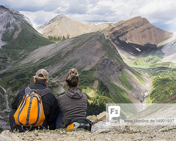 Male and female hiker sitting on a rock ridge overlooking a valley and mountain range in Kananaskis Country; Alberta  Canada