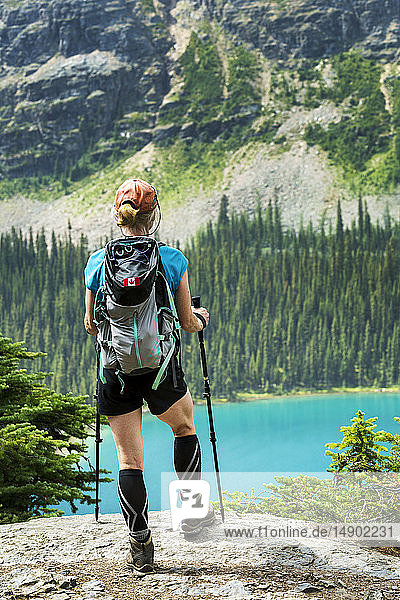 Female hiker standing on rocky cliff overlooking colourful alpine lake and mountain cliff in the background; British Columbia  Canada