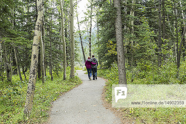 A mature couple walking on a trail with arms around each other; Kananaskis  Alberta  Canada