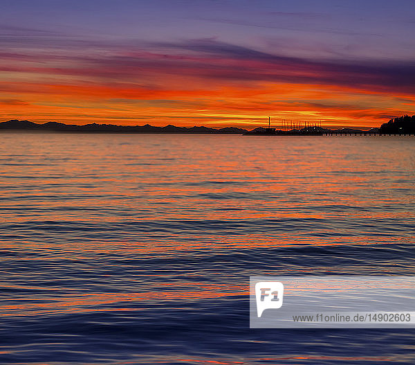 Dramatic and vibrant sunset with a silhouetted coastline; Whiterock  British Columbia  Canada