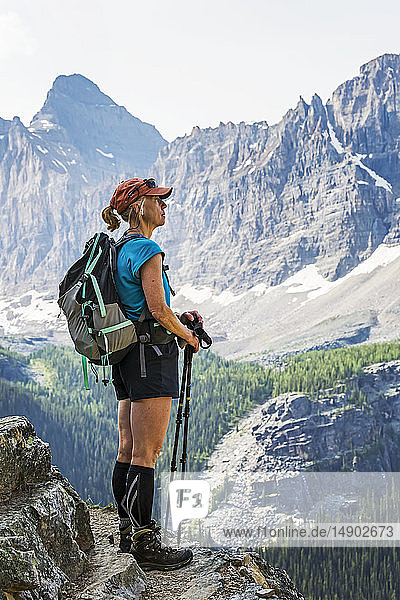 Female hiker standing on cliff edge overlooking mountains and valley; British Columbia  Canada