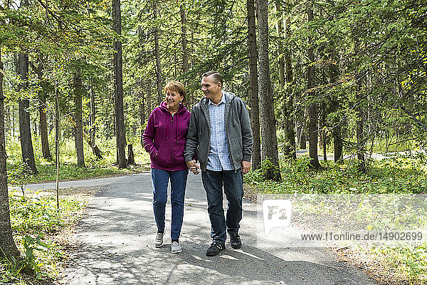 A mature couple walking on a trail holding hands; Kananaskis  Alberta  Canada