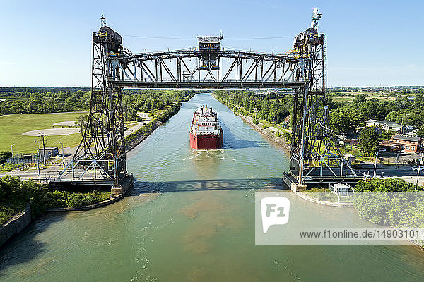 Aerial view of large laker ship navigating under a metal lift bridge in a canal with blue sky; Thorold  Ontario  Canada
