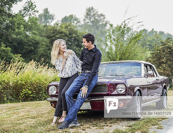 A young couple standing with a vintage sports car; Bothell  Washington  United States of America