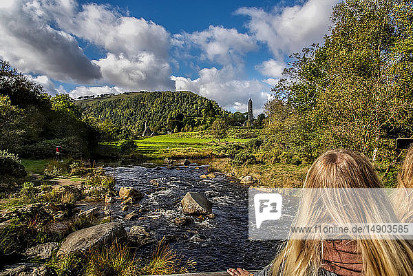 Tourists view St. Kevin's Church and round tower in the distance at Glendalough; County Wicklow  Ireland
