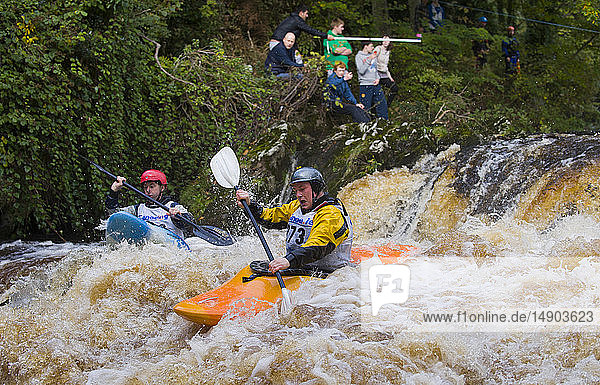 Kayaks race down rapids with spectators watching from the shoreline at the Carna Kayak event; Buncrana  County Donegal  Ireland