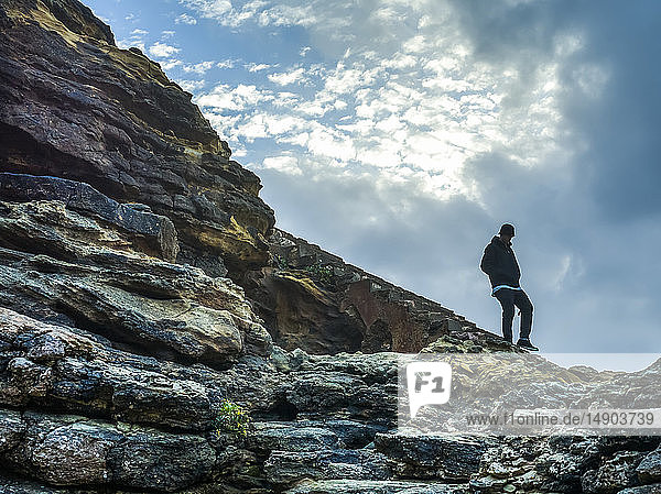 Young man walking on rocky  rugged terrain along Nazare Beach; Nazare  Leiria District  Portugal