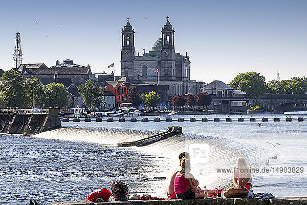 Young adults sits along the River Shannon enjoying the sunshine together with the Church of Saints Peter and Paul in the background; Athlone  County Westmeath  Ireland