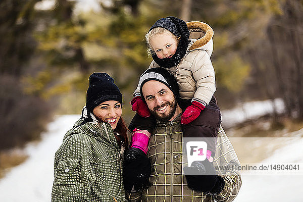 A young family hiking outdoors with their young daughter during a winter family outing: Fairmont  British Columbia  Canada