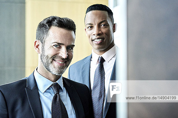 Smiling businessmen standing in hotel lobby