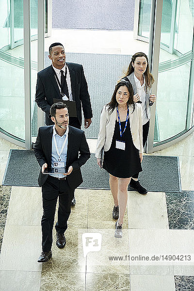 Business people entering hotel lobby