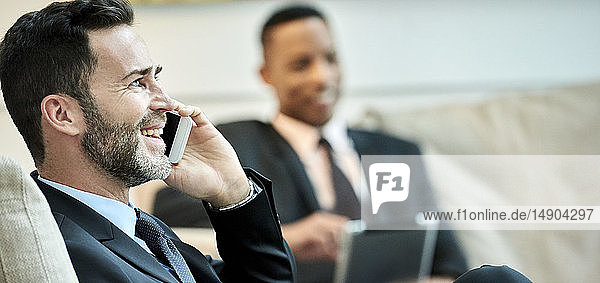 Businessman using smart phone in hotel lobby