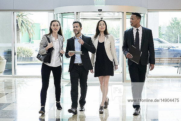 Business people talking while entering in hotel lobby