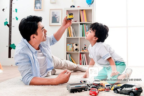 Happy father and son play in the living room