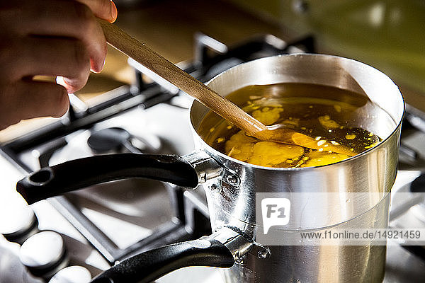 High angle close up of person melting wax for candles in saucepan on stove.