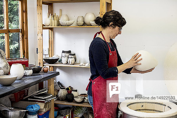 Woman wearing red apron standing in her workshop next to kiln  holding ceramic vase.