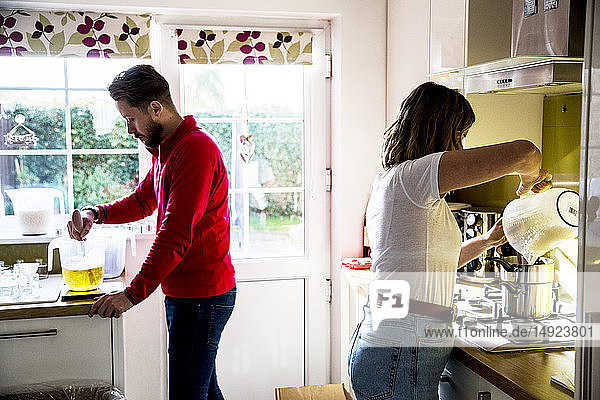 Man and woman standing in a domestic kitchen  making jar candles.