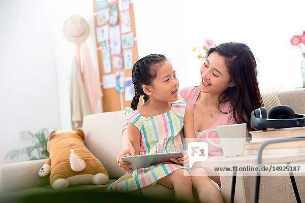 Happy mother and daughter at home watching the tablet