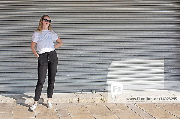 Full body photo of young casual sporty dressed blonde woman with sunglasses in white t-shirt against corrugated iron wall street style.