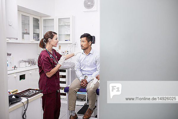 Female doctor talking with male patient in clinic examination room