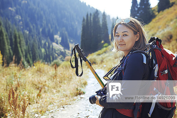 Portrait confident young female photographer backpacking on sunny trail
