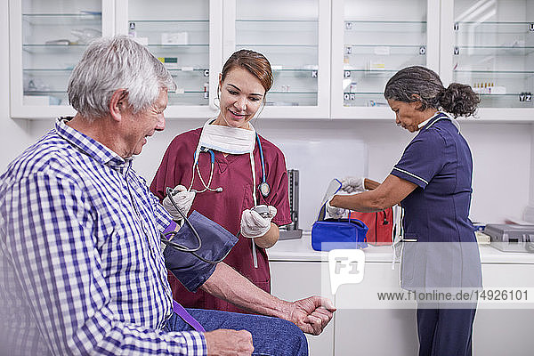 Female nurse checking blood pressure of senior male patient in clinic examination room