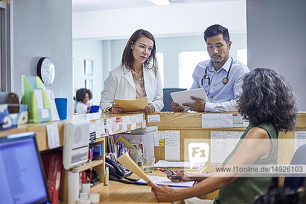 Doctors and receptionist talking in clinic