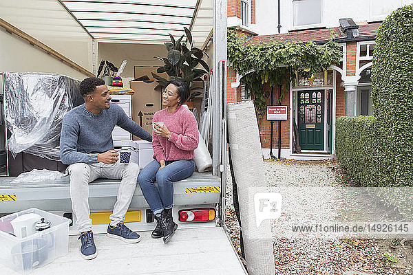 Couple talking and drinking tea  taking a break at back of moving van outside new house