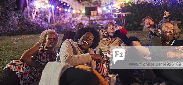 Laughing friends watching movie in backyard