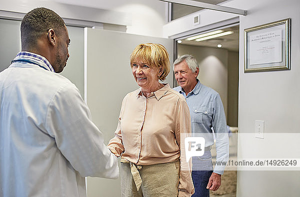 Doctor greeting senior couple in clinic doctors office