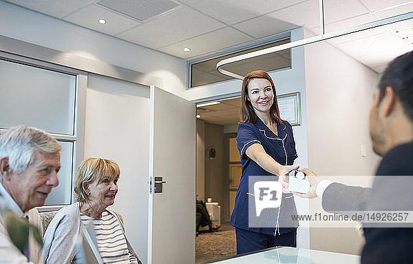 Female nurse giving medication to doctor in clinic doctors office