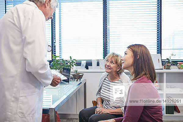 Doctor with digital tablet talking with women in doctors office