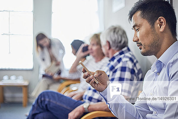 Man using smart phone  waiting in clinic waiting room