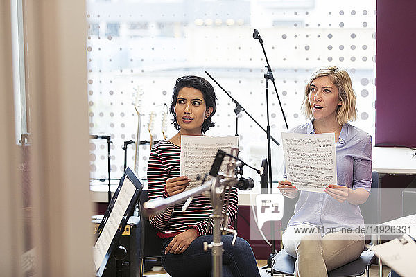 Women with sheet music singing in music recording studio