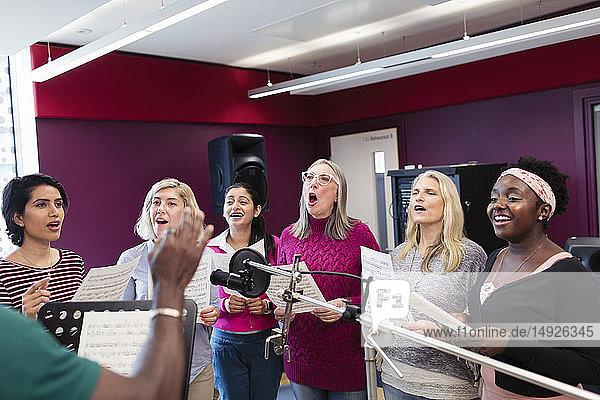 Womens choir with sheet music singing in music recording studio