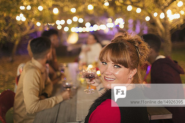 Portrait happy woman enjoying dinner garden party