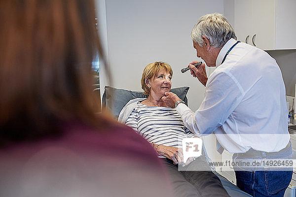 Senior doctor examining patient in clinic examination room