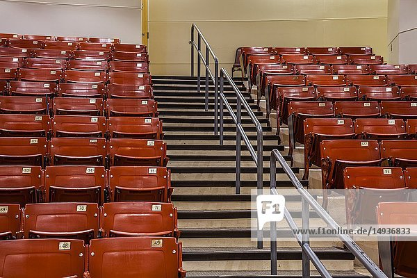 Row of empty chairs  with stairs in the middle  in an auditorium.